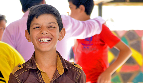 A young refugee of the Syrian civil war flashes a smile, demonstrating his resilience.