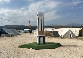 "A replica of the Clock Tower in Homs, which became the city's most famous gathering point during anti-regime demonstrations in 2011. It was built by the Syrian residents of the Katsikas refugee camp, in Greece's Epirus region. The clock is set to the time they entered the camp and a caption underneath it reads: ""Time stopped when we came here"" – September 2016 (Andres Barkil-Oteo/SyriaUntold)"